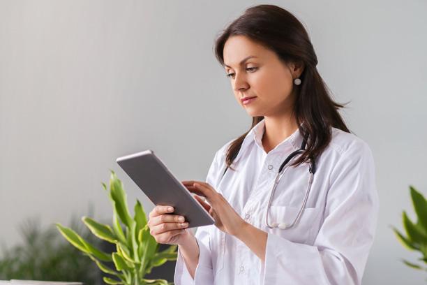 Médica segurando um tablet.