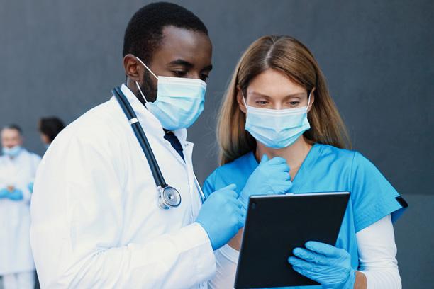Um médico e uma enfermeira, analisando dados na tela de um prontuário digital.