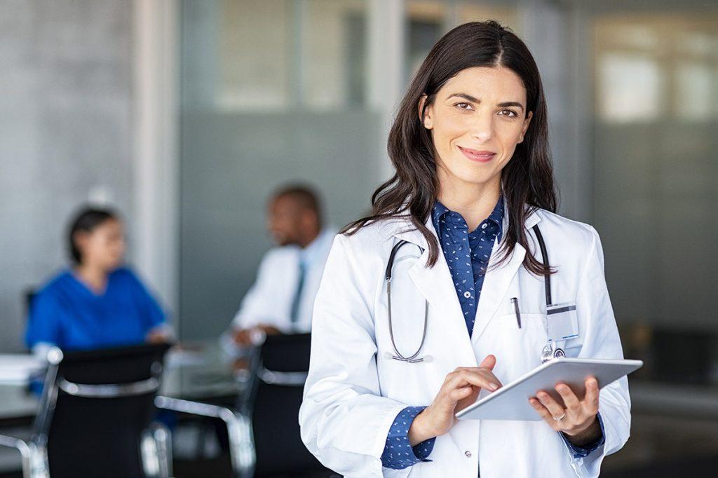 Médica feliz segurando tablet