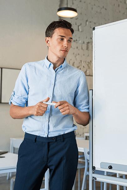 Homem ao lado de quadro branco, segurando um pincel e ventido de roupa social