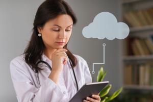 Médica olhando para o tablet usando o Gemed em nuvem